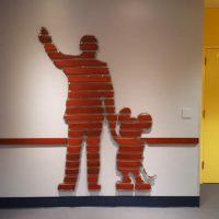 Walt holding Mickeys Hand on wall