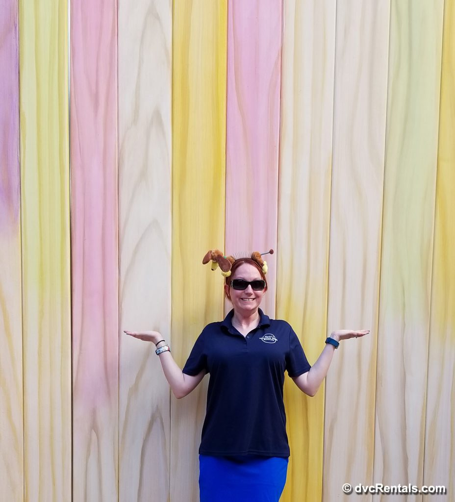 photo of team member Kelly next to the Popsicle Stick Wall