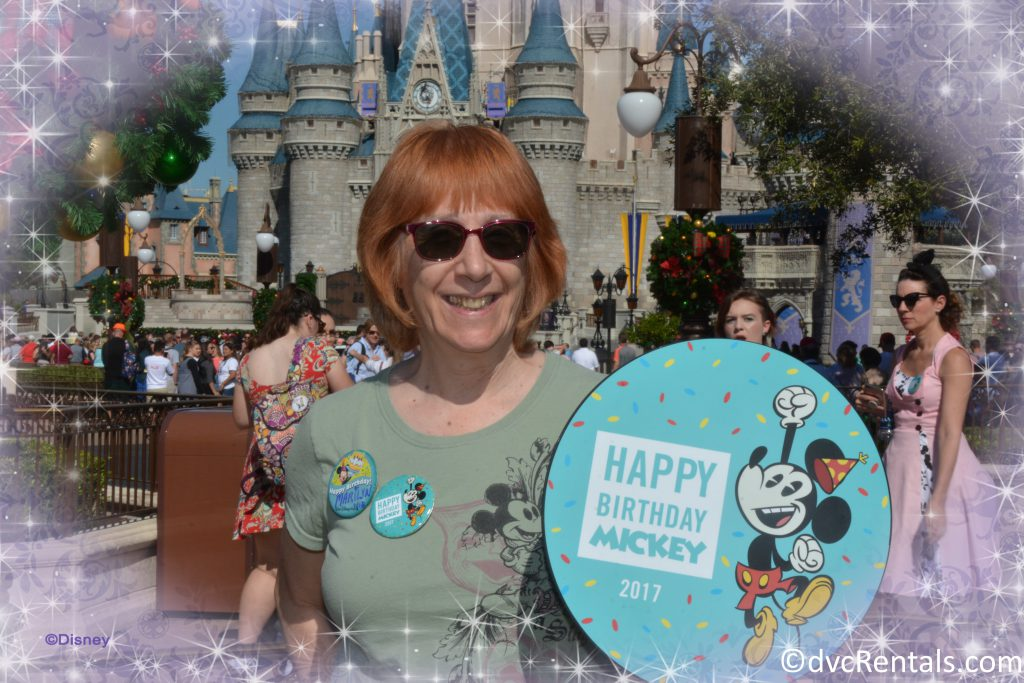 Marilyn with Happy birthday Mickey Sign in front of the Magic Kingdom