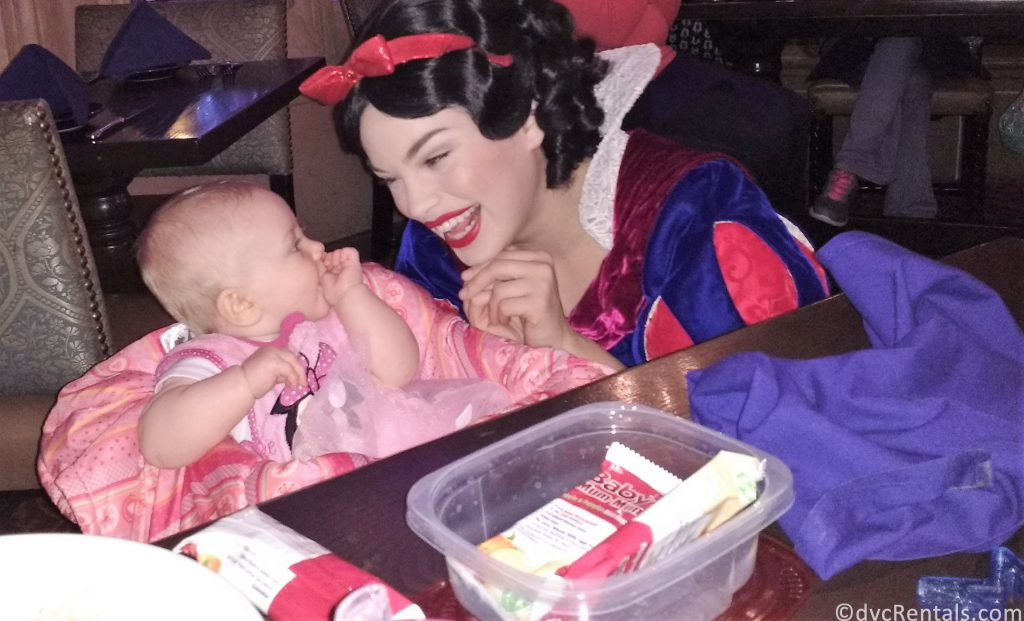 Snow White interacting with a young guest during a character dining meal