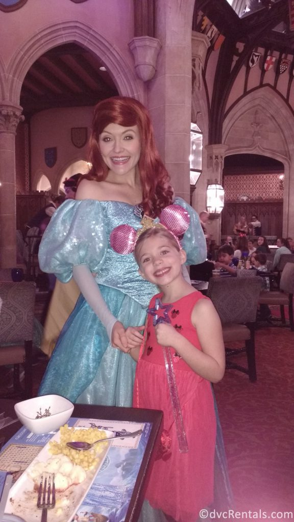 Ariel and young guest posing for a picture at Cinderella's Royal Table