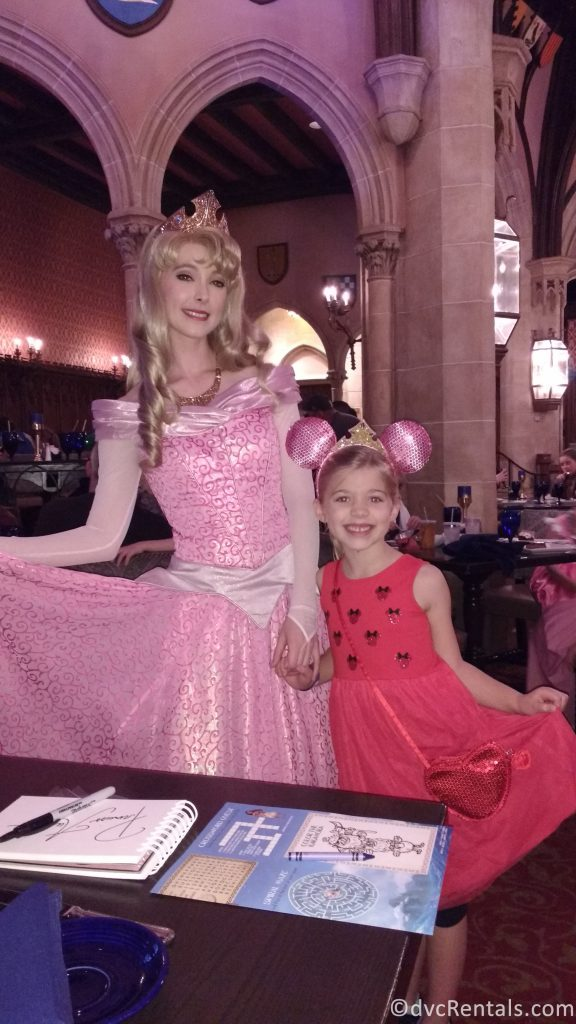 Aurora and young guest posing for a picture at Cinderella's Royal Table