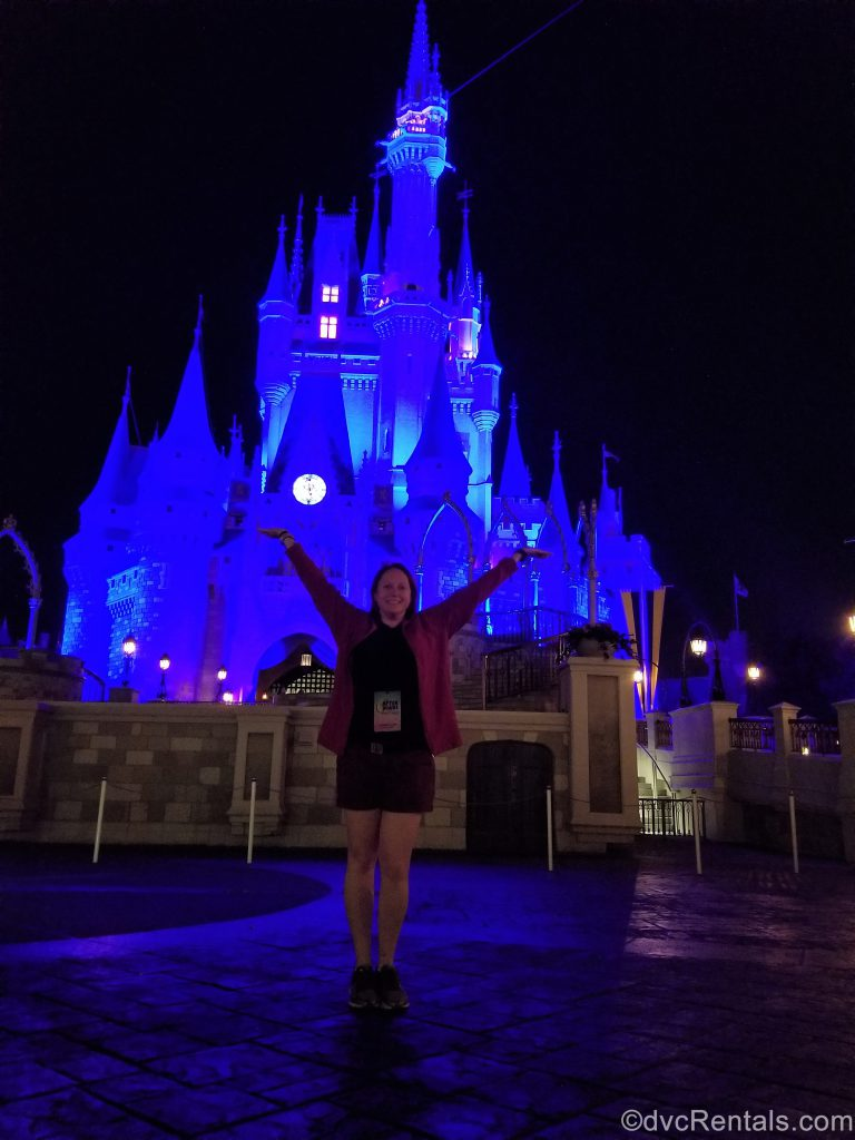 Team Member Kelly standing in front of Cinderella Castle at night with no other people around
