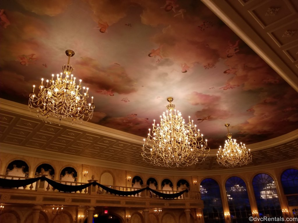 ceiling with mural and chandelier in the main dining room at Be Our Guest