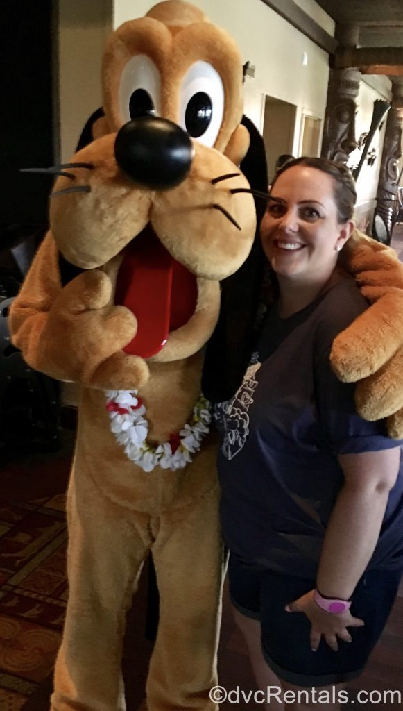 Team Member Stacy posing for a picture with Pluto