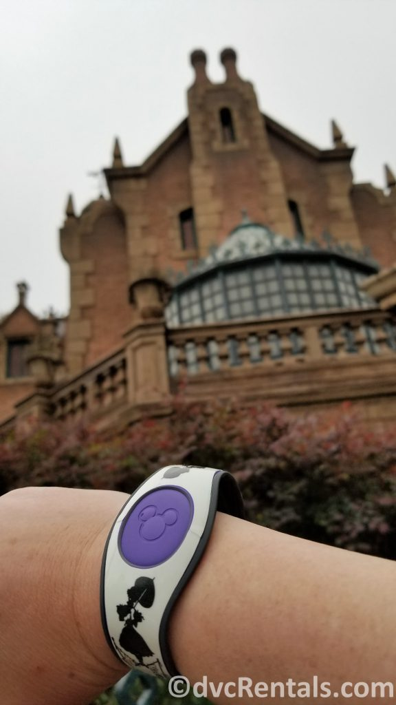 Haunted Mansion Themed Magic Band in front of the Magic Kingdom's Haunted Mansion