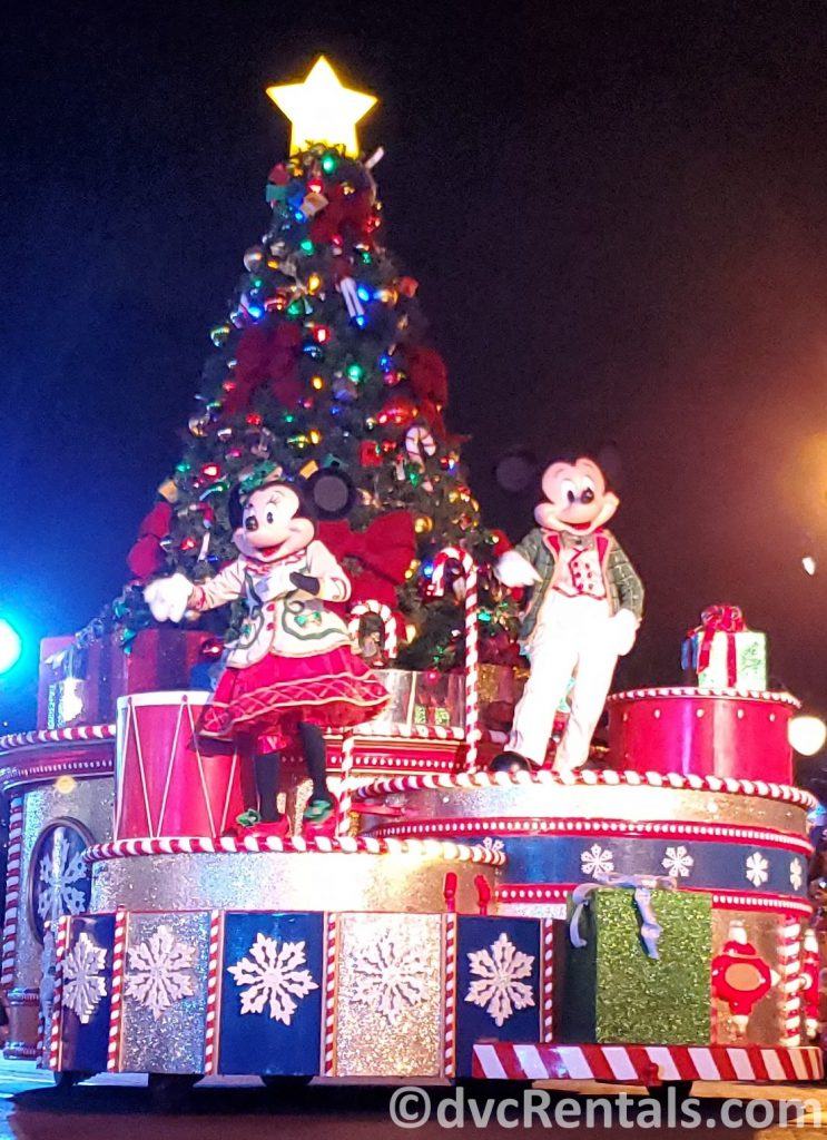 Mickey and Minnie in Christmas attire waving to guests