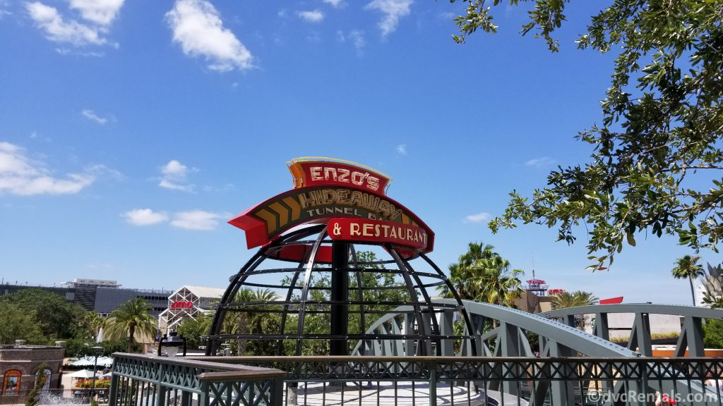Sign for Enzo's Hideaway with the AMC Theatre in the background
