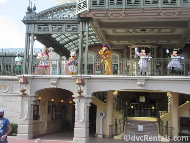Mickey Mouse and friends waving hello from the Train Station at the Magic Kingdom